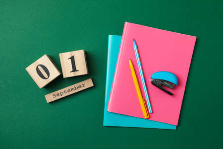 Wooden calendar with 1 september and school supplies on green background Imagens