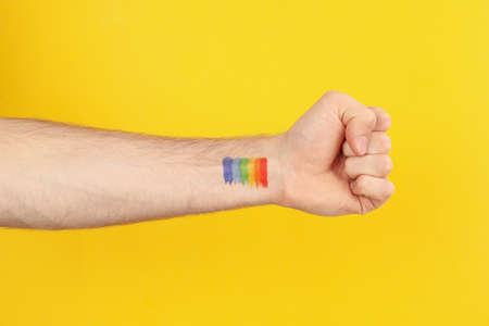 Male hand with LGBT rainbow on yellow background, space for text