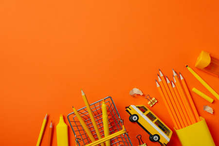 Frame of school supplies on orange background, space for text