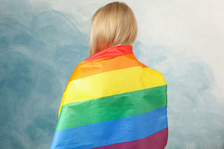 Young woman with LGBT flag against blue background Banque d'images