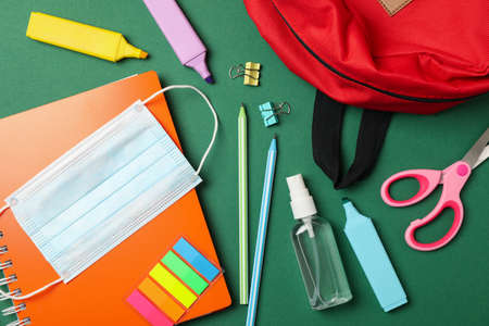 School supplies with medical mask and sanitizer on green background Imagens