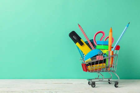 Shopping trolley with school supplies on mint background, space for text Imagens