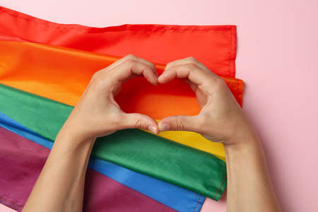 Heart made of female hands on pink background with LGBT flag