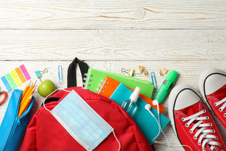 School supplies with medical mask and sanitizer on wooden background Imagens