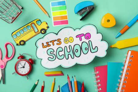 Text Let's go to school and school supplies on mint background Imagens
