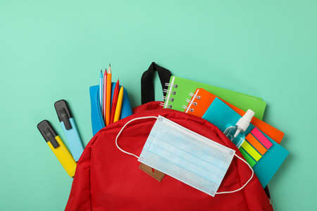 School supplies with medical mask and sanitizer on mint background