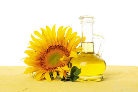 Sunflower and glass jar of oil on yellow table isolated on white background
