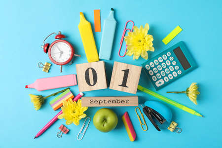 Wooden calendar with 1 september and school supplies on blue background Imagens