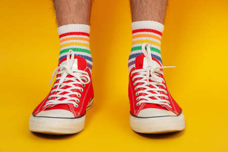 Male legs in red sneakers and LGBT socks on yellow background Banque d'images