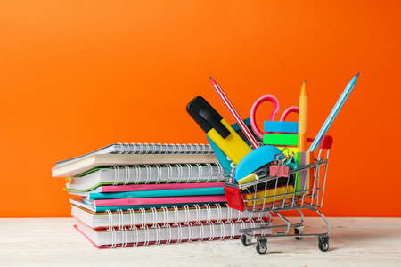 Shopping trolley with school supplies on orange background, space for text