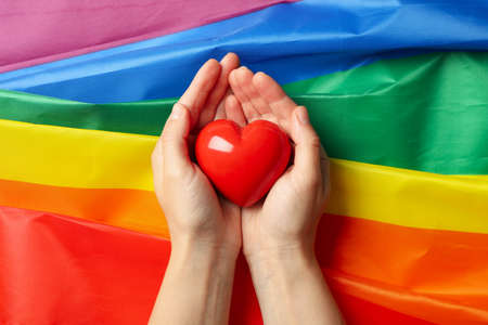 Female hands hold heart on LGBT flag, top view Banque d'images