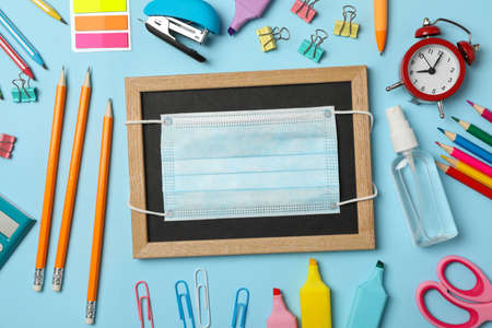 School supplies with medical mask and sanitizer on blue background Foto de archivo