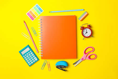 School supplies on yellow background, space for text