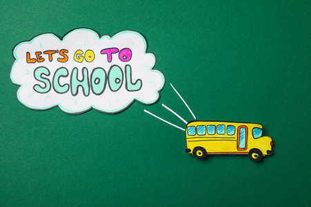 Decorative school bus and text Let's go to school on green background