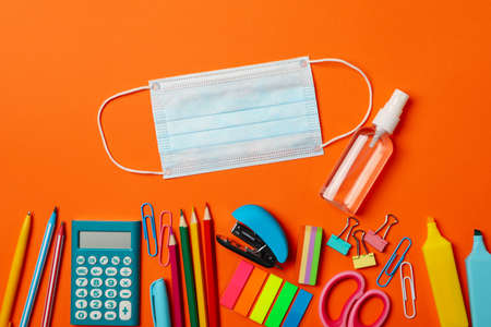School supplies with medical mask and sanitizer on orange background Imagens