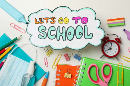 Text Let's go to school, school supplies, medical mask and sanitizer on white background