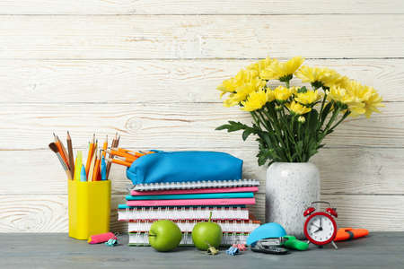 School supplies and flowers in vase on wooden background, space for text