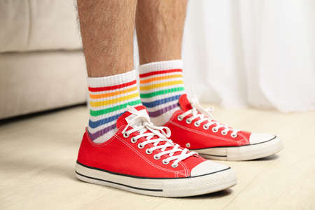Man in red sneakers and LGBT socks standing indoor Banque d'images