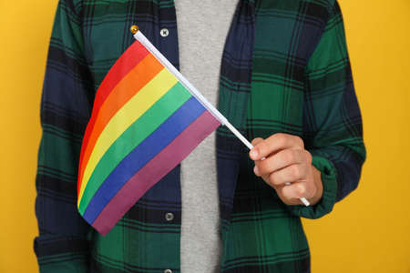 Man hold LGBT flag against yellow background Imagens