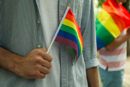 Young men with LGBT flag standing outdoor Imagens