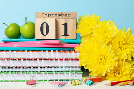 Wooden calendar with 1 september and school supplies on blue background, close up Imagens
