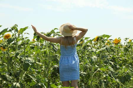 Beautiful girl in sunflower field. Summer sunny day