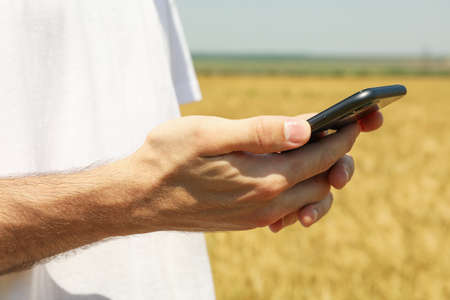 Man with phone in barley field. Agricultureure business