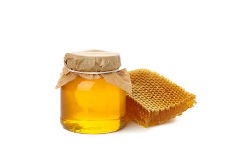 Glass jar of honey and honeycomb isolated on white background