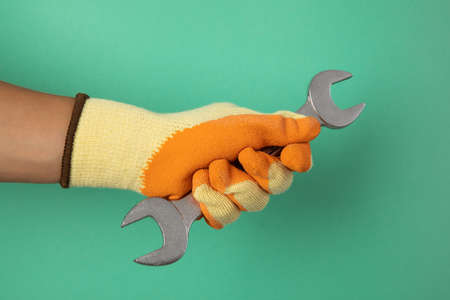 Hand in construction glove hold wrench on mint background 版權商用圖片