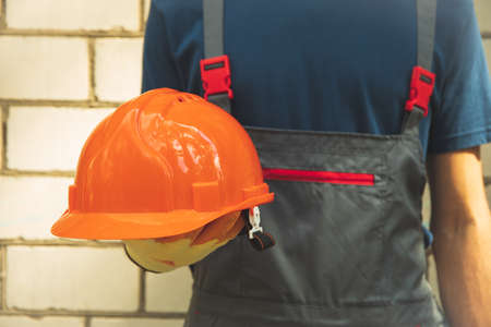 Man in overalls holds safety helmet outdoor 版權商用圖片