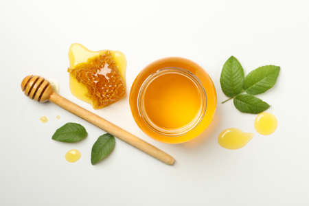 Composition with jar of honey, leaves and dipper on white background