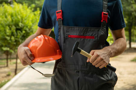 Man in overalls holds safety helmet and hammer outdoor