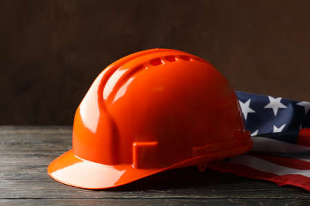 American flag and safety helmet on wooden background, close up