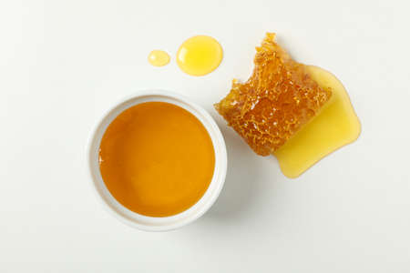 Bowl with honey and honeycomb on white background
