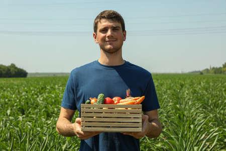 Man with wooden box of vegetables in corn field. Farming 版權商用圖片