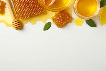 Composition with honeycombs, honey and dipper on white background
