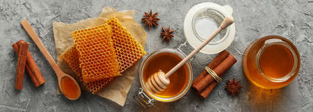 Composition with honeycombs, honey and cinnamon on gray background