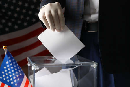 Man in glove putting ballot into voting box against american flag