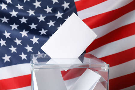 Voting box with bulletins on american flag background