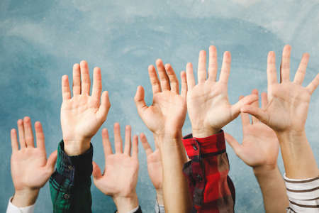 Hands of different people raised up on blue background
