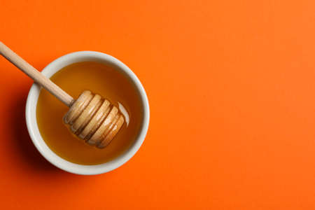 Bowl with honey and dipper on orange background, top view 版權商用圖片