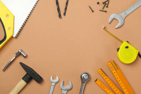 Construction tools on beige background, space for text