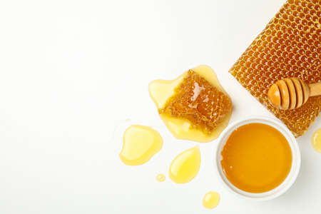 Bowl with honey, dipper and honeycombs on white background 版權商用圖片