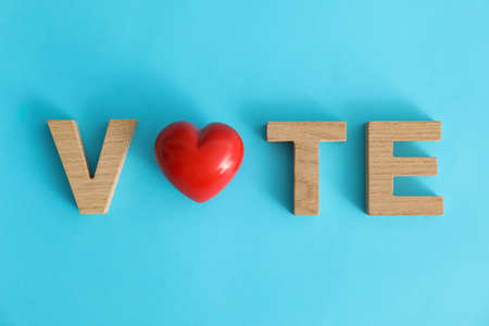 Word Vote made of wooden letters and heart on blue background Stock Photo