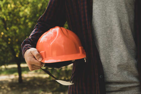 Builder in shirt and jeans holds safety helmet outdoor 版權商用圖片