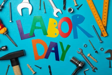 Text Labor day and construction tools on blue background