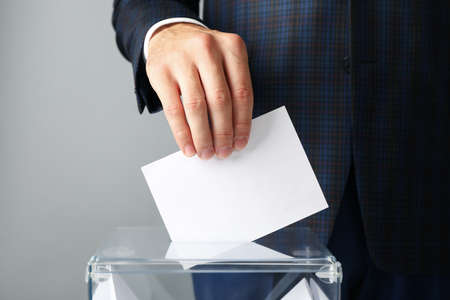 Man putting ballot into voting box against gray background