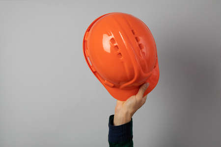Hand hold safety helmet on gray background