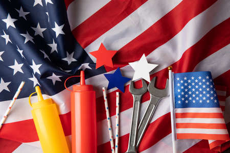 Composition with american flag, bottles for sauce and wrenches, top view