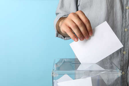Man putting ballot into voting box against blue background